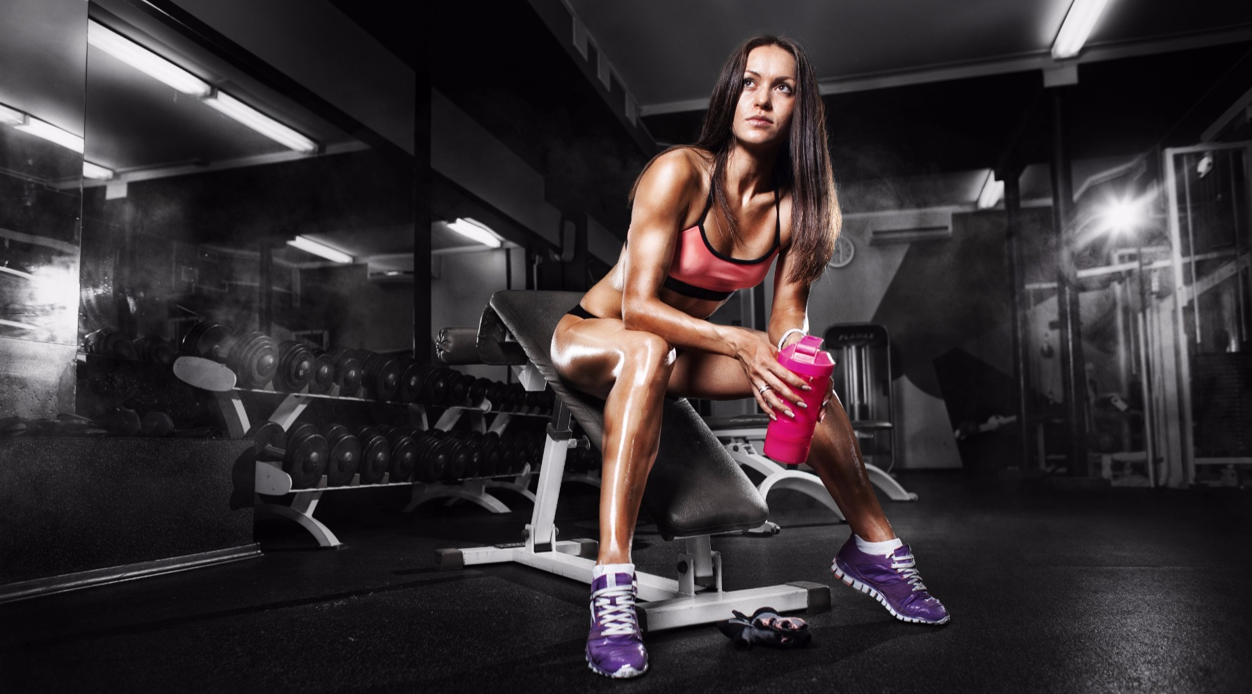 female sitting on workout bench